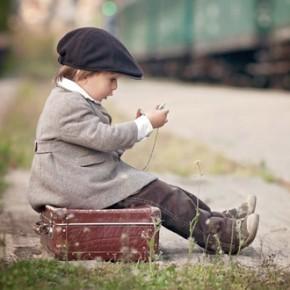 Kleiner Bub wartet auf Zug - auf Koffer sitzend